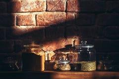 Barattoli di vetro d'annata delle spezie assortite su uno scaffale di legno Fotografia Stock