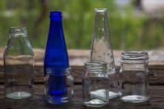 Barattoli e bottiglie vuoti sul davanzale di legno della finestra Immagini Stock