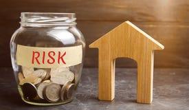 Barattolo con le monete ed il rischio di parola e una casa di legno Proprietà d'acquisto su credito Il concetto del rischio finan fotografia stock