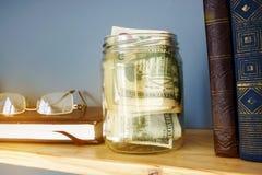 Barattolo con soldi su uno scaffale Risparmio e finanze domestiche fotografia stock libera da diritti