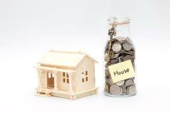 Barattolo dei soldi con le monete e la casa di legno di modello Immagine Stock Libera da Diritti