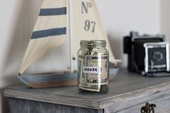 Barattolo dei soldi della Camera a casa immagine stock