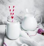 Barattolo del latte su fondo rustico di legno immagini stock libere da diritti