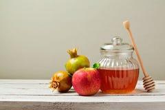 Barattolo del miele, mele rosse e melograno sul bordo di legno bianco Fotografie Stock