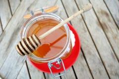 Barattolo del miele sul piatto rosso Fotografia Stock