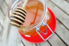 Barattolo del miele sul piatto rosso Immagini Stock