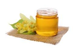 Barattolo del miele del tiglio e del tiglio di fioritura su bianco Immagine Stock