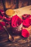 Barattolo dell'inceppamento del petalo rosa su una tavola di legno con le rose dei fiori, fuoco selettivo Immagini Stock