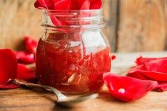 Barattolo dell'inceppamento del petalo rosa su una tavola di legno con le rose dei fiori, fuoco selettivo Fotografia Stock Libera da Diritti
