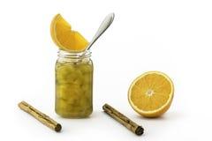Barattolo dell'inceppamento della zucca con un cucchiaio d'argento, i bastoni dei cinnamons e l'arancia immagini stock libere da diritti
