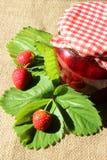 Barattolo dell'inceppamento di fragola con le fragole e le foglie Fotografie Stock