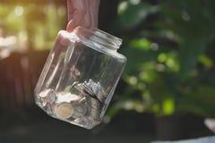 Barattolo della tenuta della mano con le monete Affare e risparmio di finanza di concetto Immagini Stock