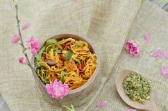 Barattolo di bambù con il pollo secco e cucchiaio con il fiore del tè e della pesca del riso fotografie stock