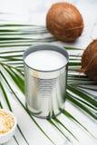 Barattolo di latta aperto con la bevanda del latte di cocco Fotografia Stock