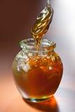 Barattolo di miele e di un cucchiaio Fotografie Stock