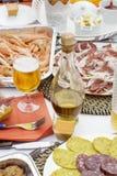 Barattolo di olio d'oliva accanto al vetro di birra ed ai piatti differenti Fotografia Stock Libera da Diritti