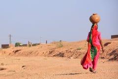 Barattolo di trasporto della donna locale con acqua sulla sua testa, villaggio di Khichan immagini stock