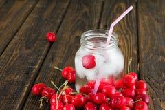 Barattolo di vetro bagnato in pieno dei cubetti di ghiaccio e delle ciliege Fotografie Stock Libere da Diritti