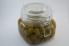Barattolo di vetro chiuso delle olive su bianco Fotografie Stock Libere da Diritti