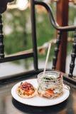 Barattolo di vetro con gli spuntini e tortino con i pomodori e la carne su un primo piano bianco del piatto Fotografie Stock Libere da Diritti