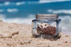 Barattolo di vetro con le conchiglie sulla spiaggia sabbiosa, tempo di vacanza fotografia stock