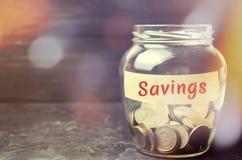 """Barattolo di vetro con le monete e l'iscrizione """"risparmio """" Il concetto di accumulazione dei soldi nel bilancio familiare Assicu fotografia stock"""
