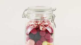 Barattolo di vetro con molte caramelle dolci luminose stock footage
