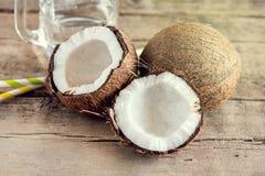 Barattolo di vetro e del noce di cocco con il vecchio fondo di legno Straw Toned dell'acqua di cocco Fotografie Stock