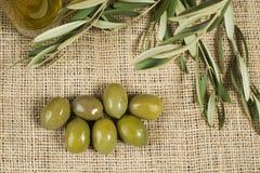 Barattolo di vetro e foglie dell'olio d'oliva vergine con le olive fresche sul burla immagini stock