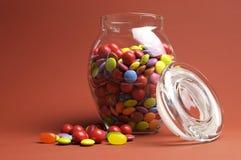 Barattolo di vetro in pieno dei lecca lecca e della caramella variopinti luminosi con il coperchio aperto Fotografie Stock Libere da Diritti
