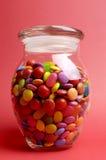 Barattolo di vetro in pieno dei lecca lecca e della caramella variopinti luminosi con il coperchio chiuso Fotografia Stock Libera da Diritti