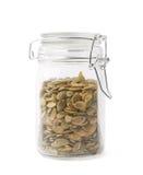 Barattolo di vetro riempito di semi di zucca Immagine Stock