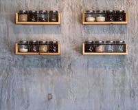 Barattolo di vetro sugli scaffali di legno su calcestruzzo di legno fotografie stock