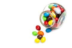 Barattolo di vetro trasparente con le caramelle di cioccolato variopinte sulla b bianca Fotografie Stock