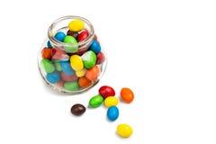 Barattolo di vetro trasparente con le caramelle di cioccolato variopinte sulla b bianca Fotografia Stock