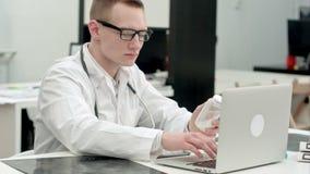 Barattolo maschio della tenuta di medico delle pillole e della prescrizione di battitura a macchina sul computer portatile stock footage