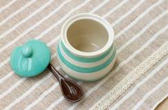 Barattolo pastello verde della porcellana e cucchiaio marrone Fotografia Stock Libera da Diritti