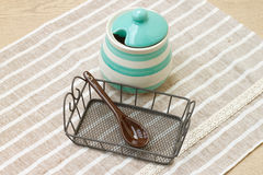 Barattolo pastello verde della porcellana e cucchiaio marrone con il tessuto di cotone Fotografie Stock