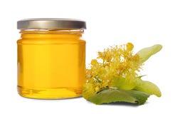 Barattolo pieno con il miele del tiglio ed il tiglio di fioritura su bianco Fotografie Stock