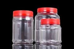 Barattolo traslucido del PVC della plastica con la copertura rossa isolata nel nero Immagini Stock
