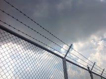 Barb-Draht und -dunkle Wolke Stockfoto