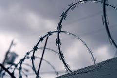 Barb wire with dark skies. A section of barbed wire installed on a wall with a dark sky as background royalty free stock images