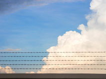 Barb wire fence and blue sky Royalty Free Stock Photo