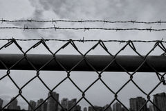 Barb Wire Fence in City in Moody Shot Stock Images