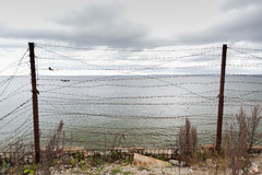Barb wire fence over gray sky and sea Royalty Free Stock Photos