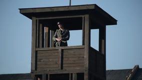 Barb Wire Fence Un soldado alemán joven con una situación del rifle en una atalaya y la mirada alrededor Visi?n inferior Guerra m almacen de video