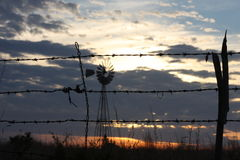 Barb Wire Knot. Sunset in West Texas thru a Barb wire fence and Windmill stock photos