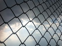Barb wire network in the sky. Background ; beautiful ; black cloud ; blue ; blue sky ; cloud ; fence ; fort ; hurdle; iron ; net ; network; stacheldraht Stock Images