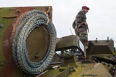 Barb wire roll and a soldier on armored vehicle Royalty Free Stock Photos
