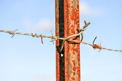Barb wire on rusty steel post Stock Image